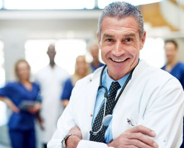 Portrait of cheerful doctor in a hospital standing with arms crossed.