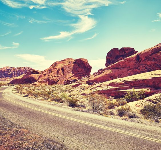 Vintage toned deserted road, travel concept, Valley of Fire, Nevada, USA.