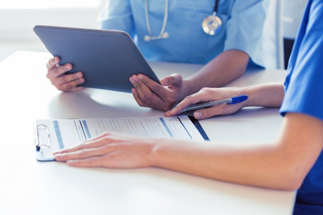 close up of doctors with tablet pc at hospital